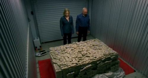 A man and woman are staring at a pile of money inside a self storage unit.