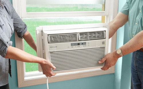 Two people installing an air conditioner into a window.