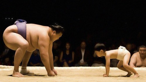 A man and a boy are on all fours, about to sumo wrestle each other.