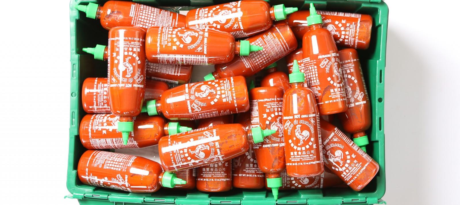A MakeSpace storage bin full of 63 Sriracha bottles.