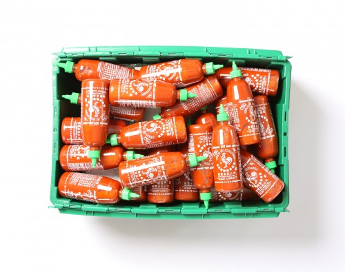 A MakeSpace storage bin full of 63 Sriracha bottles.