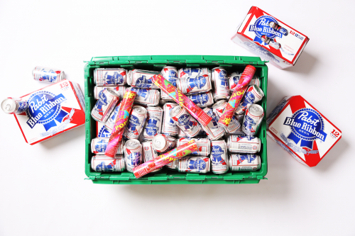 A MakeSpace storage bin is full of free beer from PBR and surrounded by cases of Pabst Blue Ribbon.