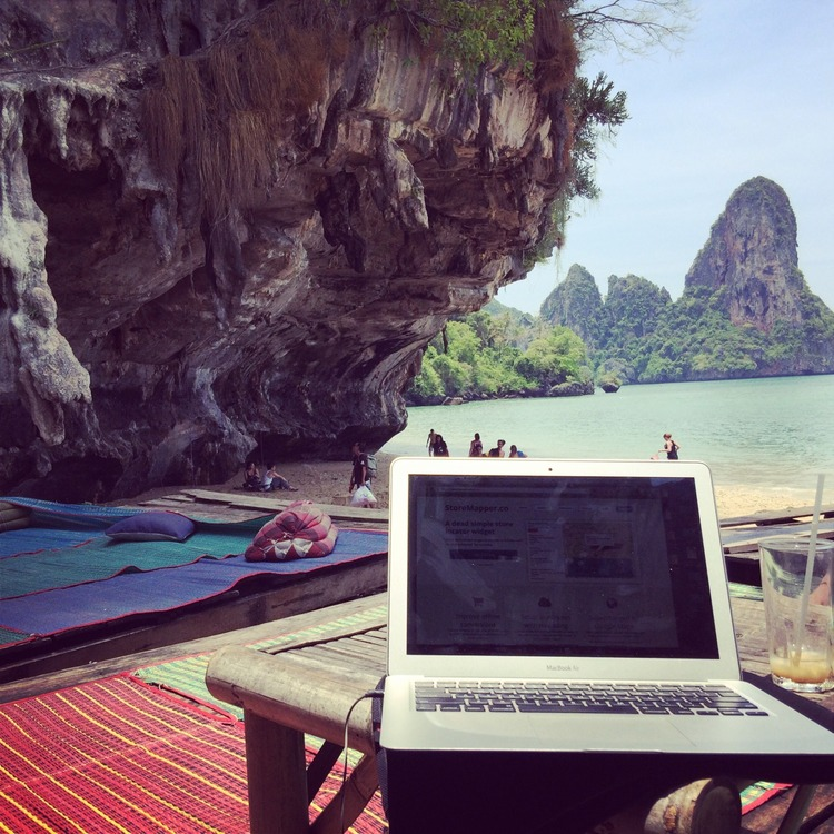 A MacBook Air and an empty glass on a wooden table at a gorgeous beach with cliffs, trees, and clear water in the background.