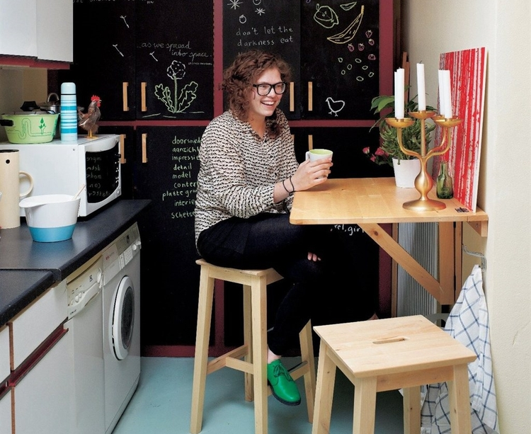 A woman is sitting on a wooden stool and holding a coffee mug in her hand in a home office that doubles as a kitchen with a wall-mounted table.
