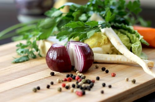 vegetables on a cutting board for cooking in a small kitchen