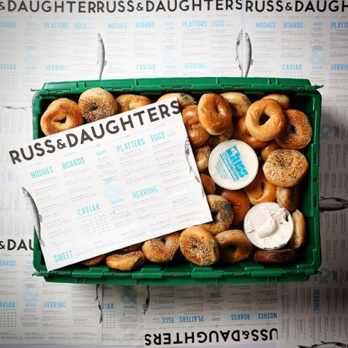A green MakeSpace storage bin is full of assorted Russ & Daughter's bagels.