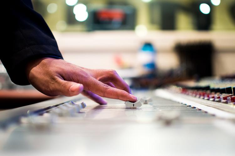 A closeup of a mixing console in a recording studio control room.