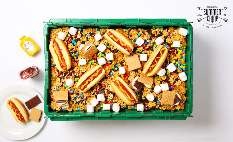 A green MakeSpace storage bin full of hot dogs, s'mores, M&Ms, pretzels, marshmallows, chocolate, and more.