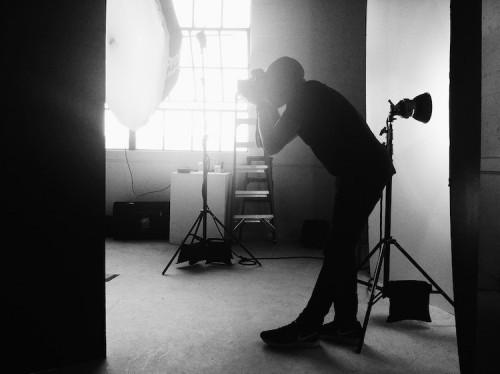 Ike Edeani, who uses MakeSpace for valet storage in NYC, takes a photo in a photography studio.