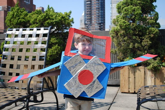A boy is wearing a blue, red, and silver cardboard box airplane Halloween costume.
