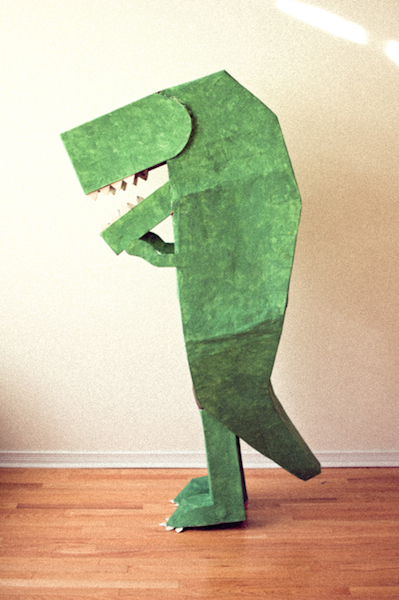 A person is wearing a green cardboard dinosaur Halloween costume.