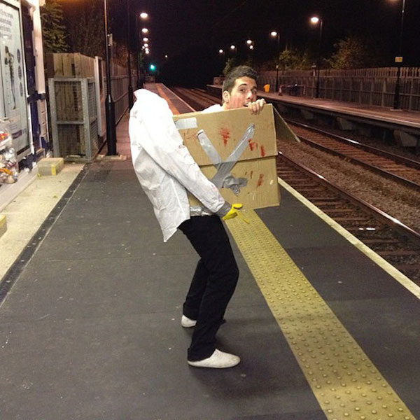 A man is wearing a head-in-box Halloween costume and standing on a platform at a train station.