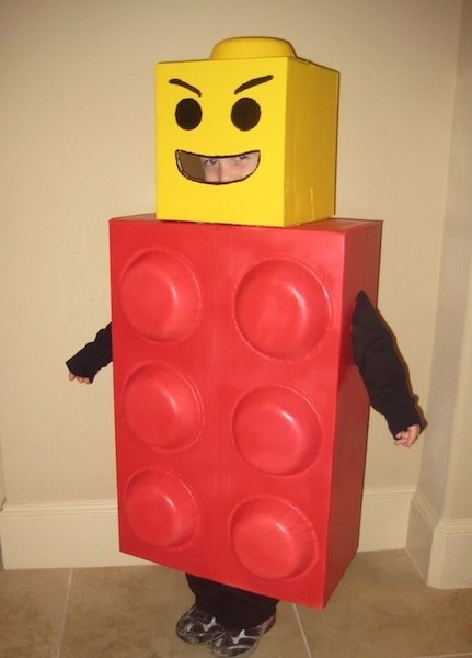 A boy is wearing a red and yellow LEGO man Hallween costume.
