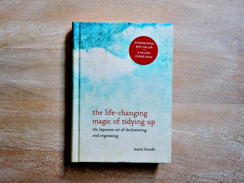 Marie Kondo The Life-Changing Magic of Tidying Up book on a wooden surface.