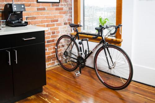 CLUG bike storage rack is storing a black bike inside a tiny kitchen.