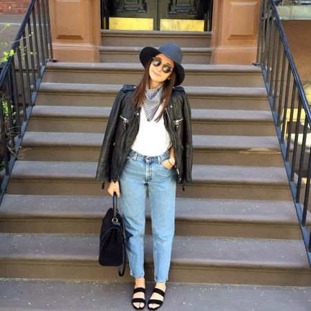 Alyssa Wasko is standing in front of a stoop and wearing a black hat, sunglasses, leather jacket, bag, shoes, and Donni Charm scarf