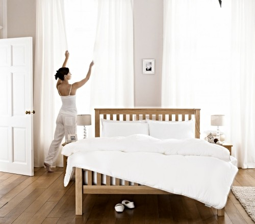 A woman dressed in white is closing her white bedroom curtains.