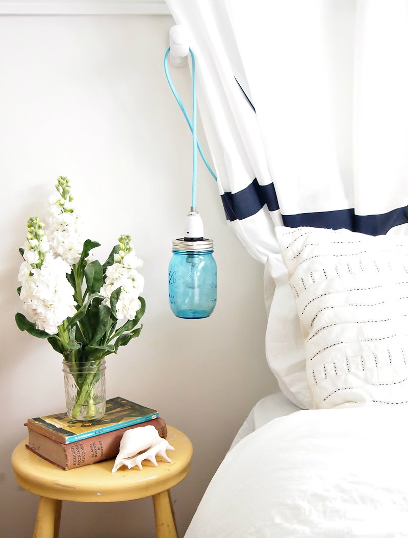A DIY mason jar pendant light is a soothing reading light or nightlight for a bedroom in a tiny apartment.