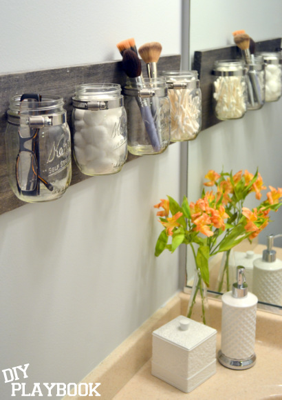 A DIY mason jar organizer is the best bathroom storage for toiletries,  brushes, eyeglasses, and plants in a small apartment.