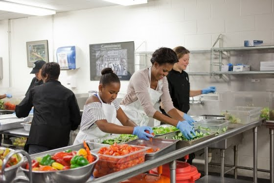 MicroGreens founder Alli Sosna removes ingredients from food storage containers to make salads with Michelle Obama at DC Central Kitchen in Washington DC.