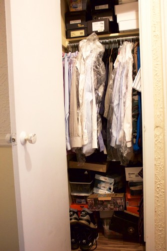 An unorganized bedroom closet stuffed with dress shirts and shoe boxes.