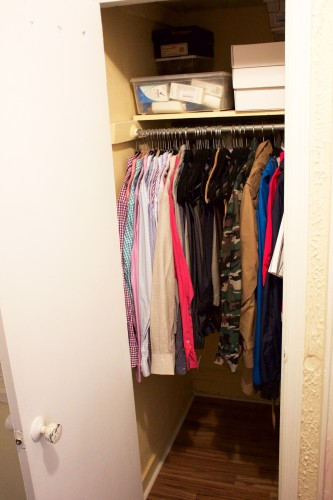 An organized, decluttered bedroom closet with shirts, jackets, and pants hanging and storage containers stacked neatly on a shelf.