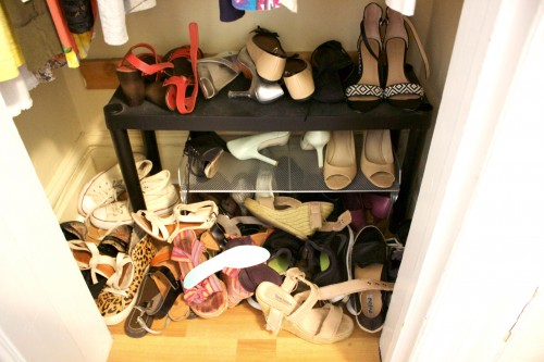 An unorganized, cluttered bedroom closet with shoes scattered everywhere.