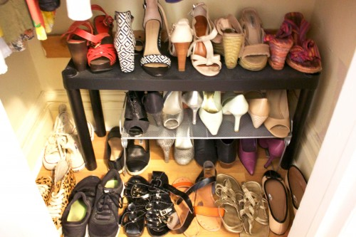 A tiny apartment's organized bedroom closet with shoes facing opposite directions on the floor, a rack, and table.