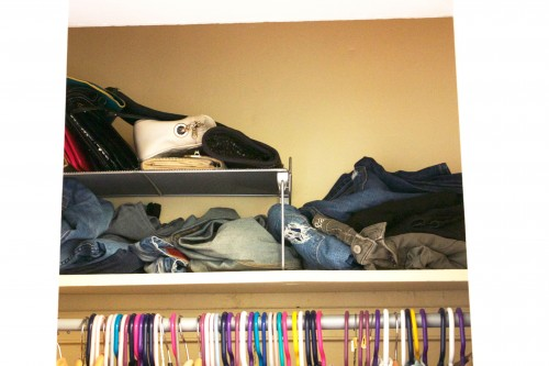 A tiny apartment's cluttered, unorganized bedroom closet with jeans scattered on a shelf.