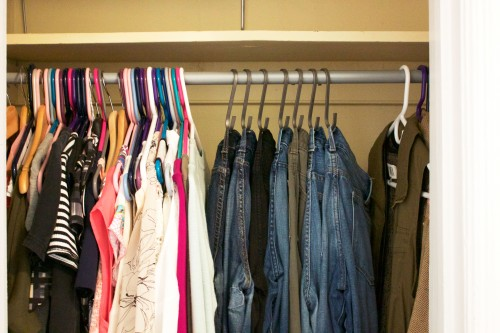 A clean, organized bedroom closet with jeans hanging on hooks and shirts on hangers.