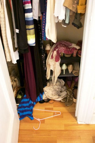 A small apartment's unorganized bedroom closet with messy shirts on the floor.