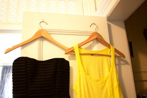 Black and yellow tops hanging neatly on wooden hangers on an organized bedroom closet's door.