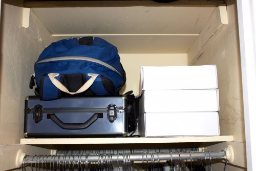 A blue backpack, a blue storage container, and three white boxes stacked on an unorganized bedroom closet shelf.