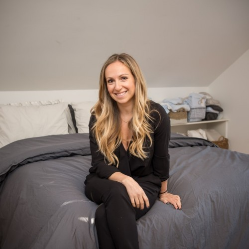 Parachute Founder and CEO Ariel Kaye, who is a MakeSpace NYC storage customer, is sitting on a made bed.