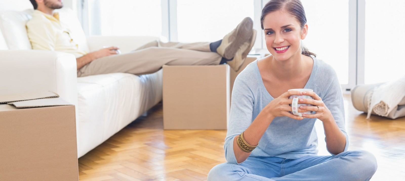A woman is sitting on the floor of an apartment and holding a coffee mug while a man is sitting on a couch with his feet atop moving boxes.