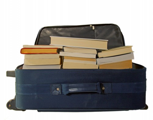 Rolling luggage filled with stacks of books makes packing and moving to a new apartment simpler.