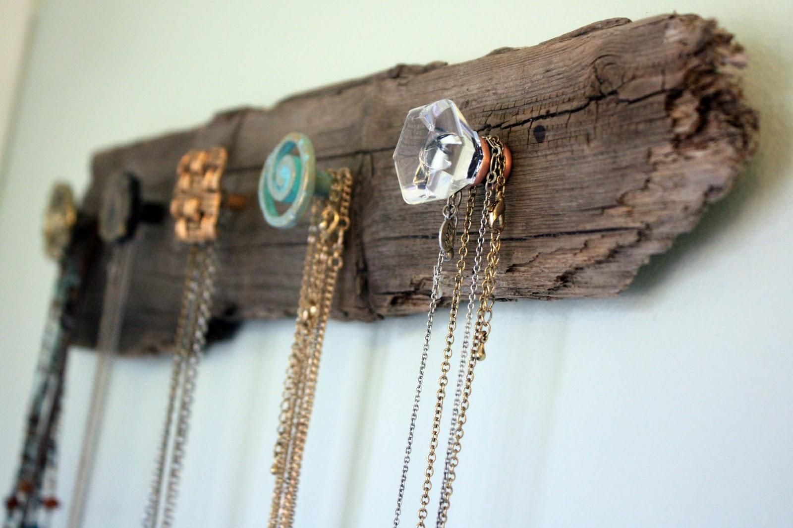 A DIY wood pallet jewelry holder used for necklace storage.