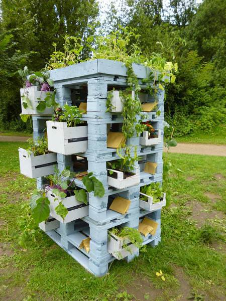 A DIY planter tower made from reclaimed wood pallets with plant storage.