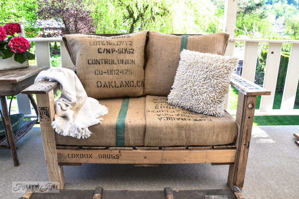 A cozy DIY wood pallet chair with a pillow and a throw blanket on top for comfort.