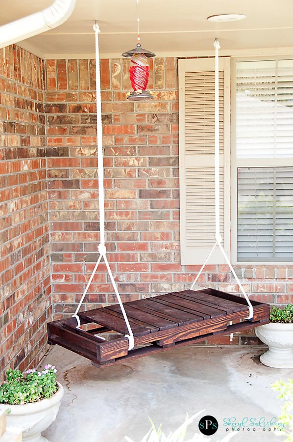 A DIY wooden shipping pallet swing on a porch.