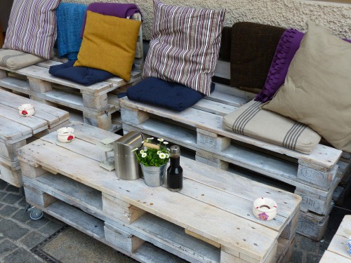 DIY wood pallet patio furniture with colorful cushions and storage space.