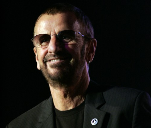 The Beatles drummer Ringo Starr is holding a microphone and wearing sunglasses, a blazer, and a t-shirt.