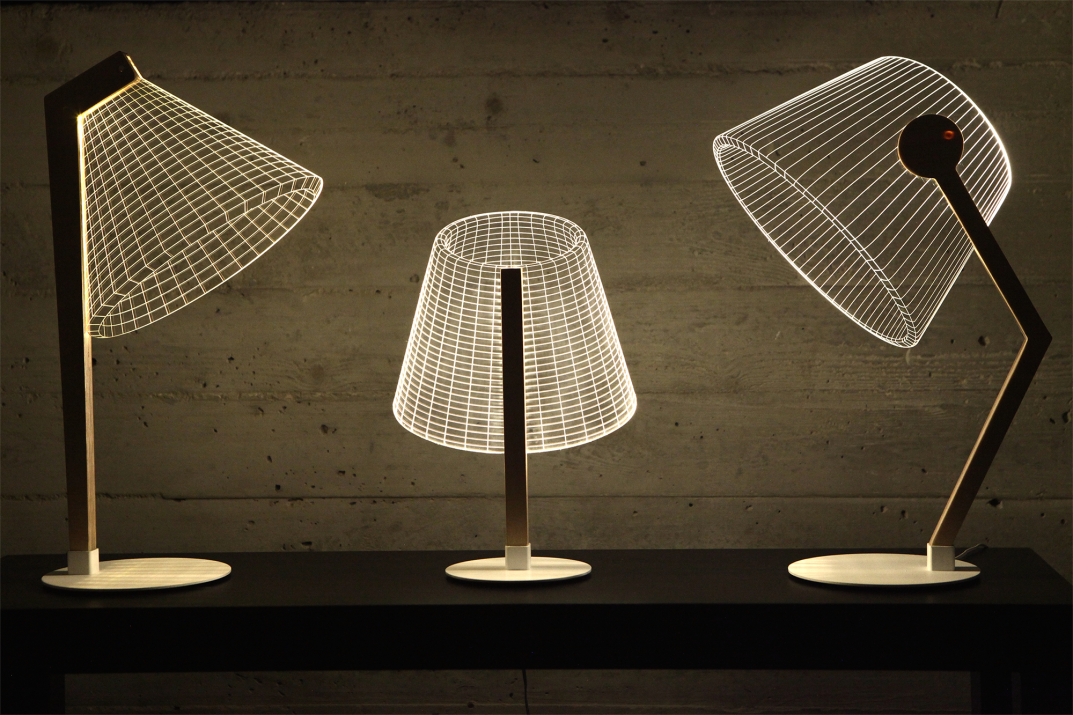 Three Studio Cheha 2D/3D BULBING lamps, the DESKi, CLASSi, and ZIGGi are on a desk in a small apartment.