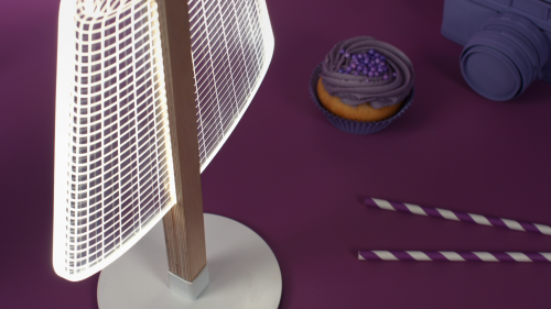 Studio Cheha's CLASSi BULBING lamp is on a table and illuminating a cupcake, camera, and straws.