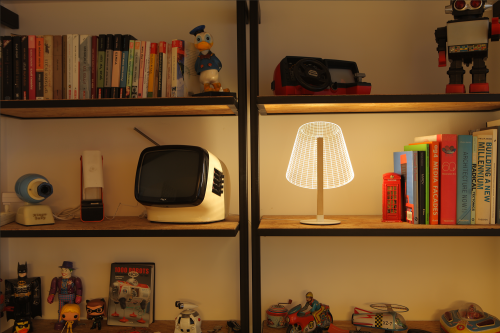 Studio Cheha's 2D/3D CLASSi BULBING lamp is on a storage shelf next to books, a retro TV, an old video game console, Batman, Joker, Donald Duck, robots, a red telephone box, and other toys.