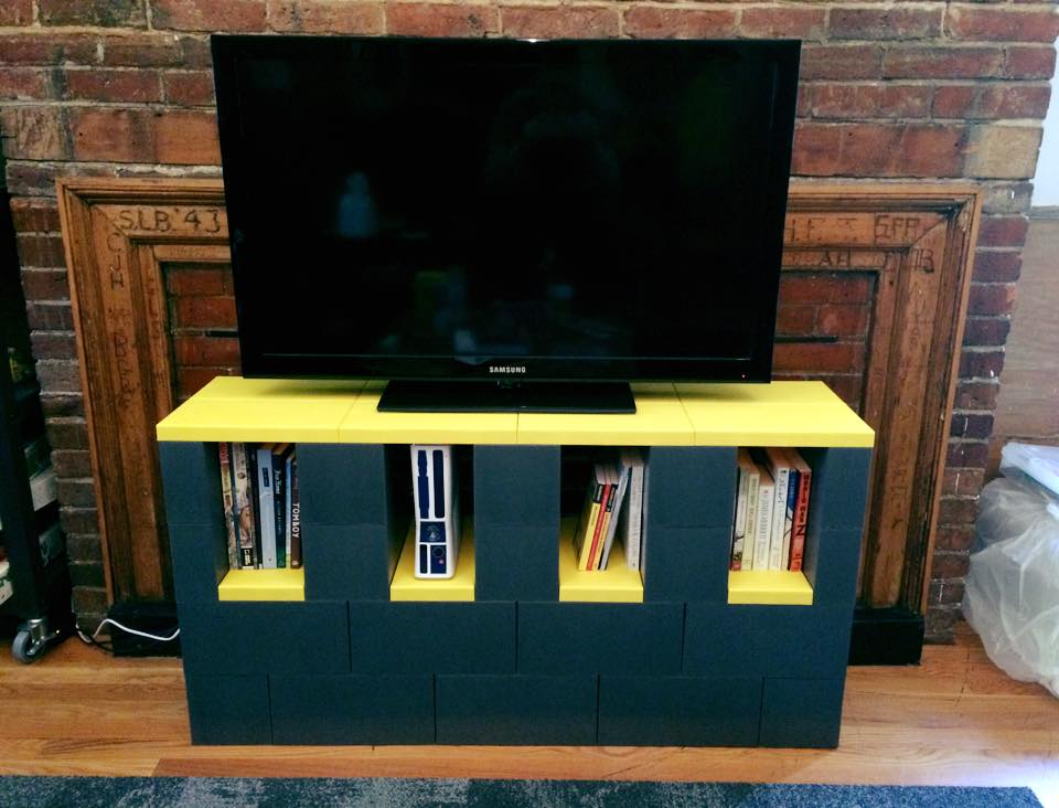 A TV stand with storage made of EverBlocks that resemble big LEGOs.