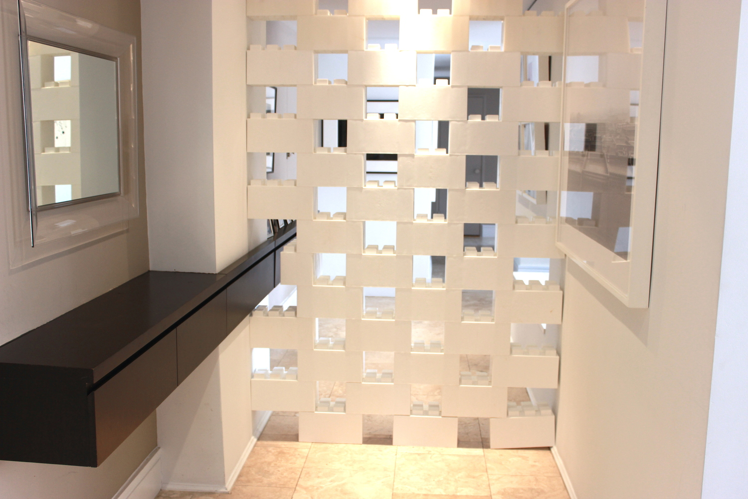 A white divider wall made of staggered EverBlocks, which are basically life-size LEGOs.