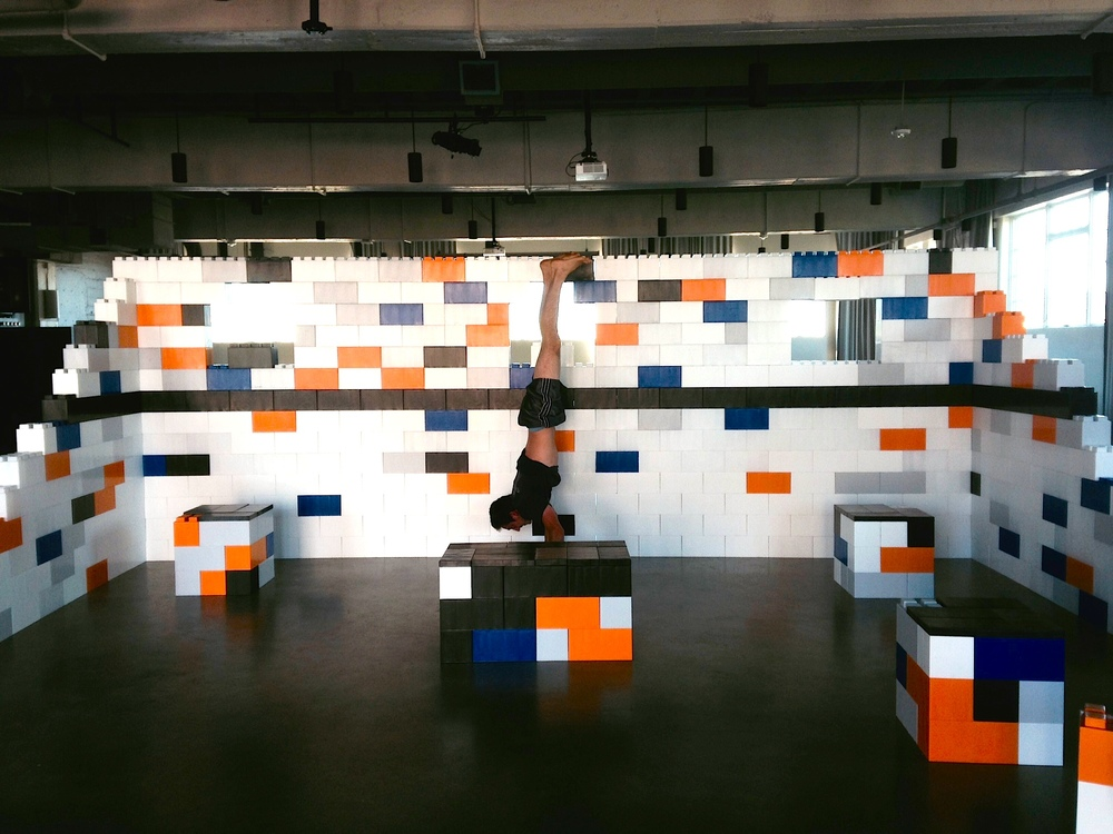 A man doing a handstand in a homa yoga studio made of big LEGO-resembling EverBlocks.