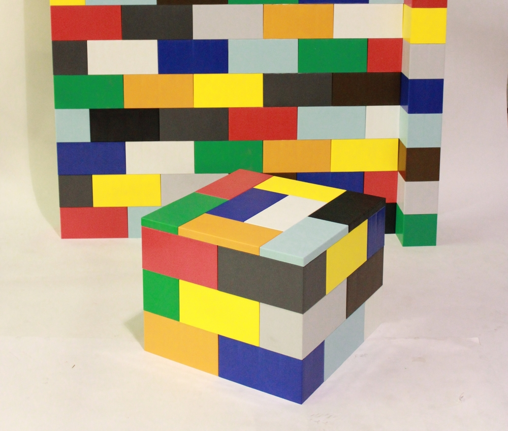 A multicolor wall and cube made of EverBlocks that resemble big LEGOs.