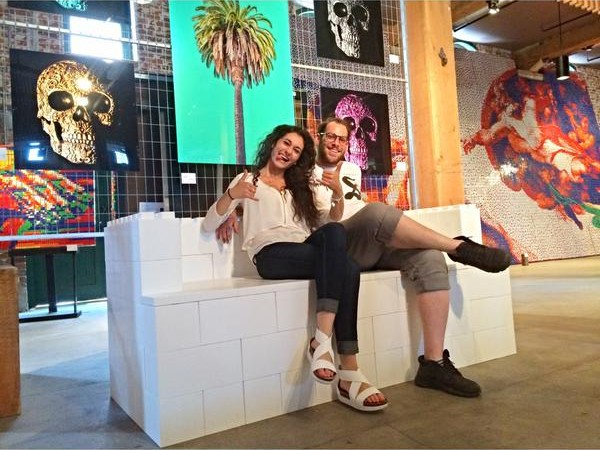 A woman and man sitting on a white sofa made of EverBlocks, which look like big LEGOs.